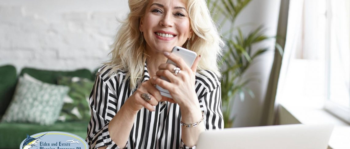elder attorney - Mature woman holding mobile phone at laptop